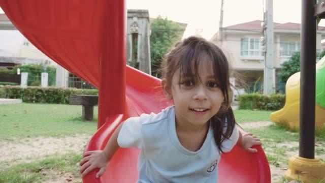 vidéos et rushes de sœur et son frère s'amuser en glissant sur un toboggan en parc. - toboggan