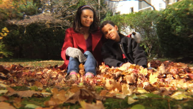 stockvideo's en b-roll-footage met ws sister (12-13) and brother (8-9) sitting together in yard / montclair, new jersey, usa - 12 13 jaar