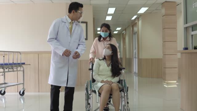 病院の廊下で車椅子で患者と一緒に歩く姉妹と医師。 - 依存点の映像素材/bロール