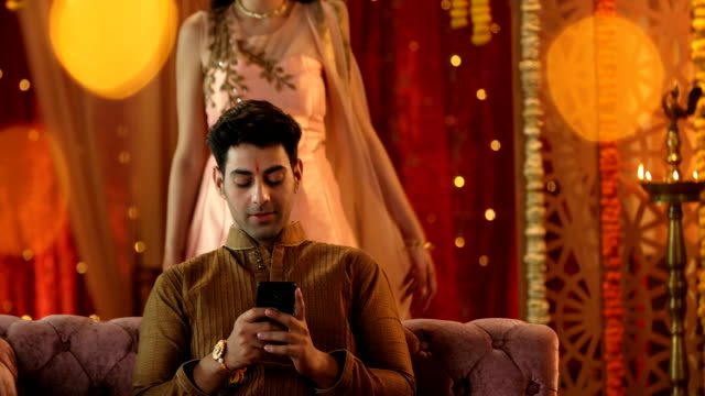 vídeos de stock, filmes e b-roll de ms sister covering brother's eyes while he uses smart phone on sofa / delhi, india - mãos cobrindo olhos