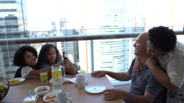 vídeos de stock, filmes e b-roll de irmã filmando pais durante café da manhã em casa - miscigenado