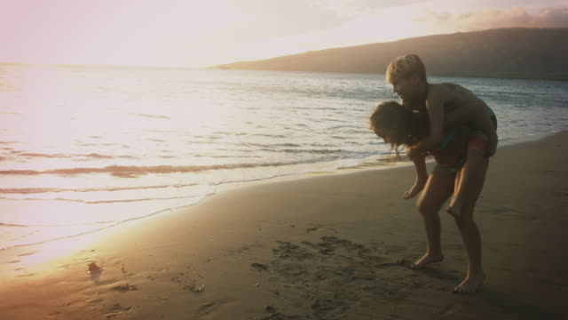 vídeos de stock e filmes b-roll de sister gives her brother a piggy back ride into the ocean. - irmão