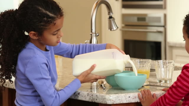 MS DS Sister Helps Pour Milk in Kitchen for Breakfast/ Richmond, Virginia USA