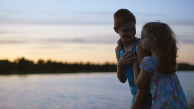 MS. Sister hugs brother on camping trip by scenic lake. They share a cute kiss and run off into the sunset.