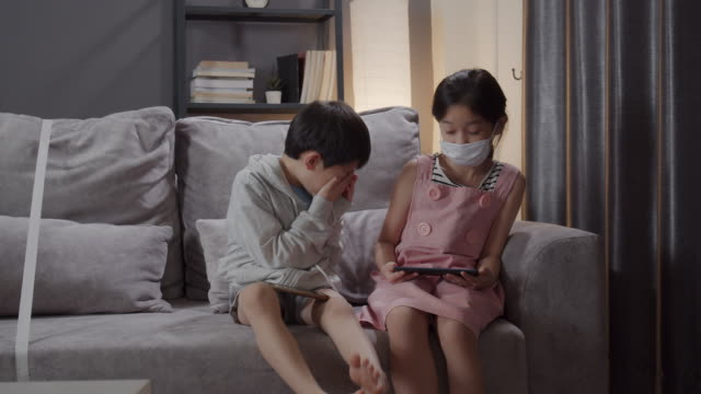 sister runaway when his brother sneezing while playing smart phone in the living room at home reduce germ spread concepts - sneezing stock videos & royalty-free footage