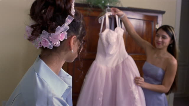 sisters admiring pink quinceanera dress in bedroom - nur weibliche teenager stock-videos und b-roll-filmmaterial