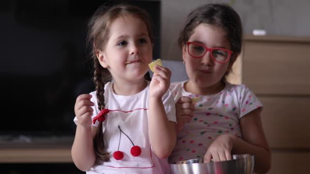 vídeos y material grabado en eventos de stock de hermanas en casa divirtiéndose - patatas fritas de churrería