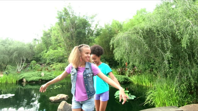 vídeos de stock e filmes b-roll de sisters at park balance on wall along pond - 12 13 years
