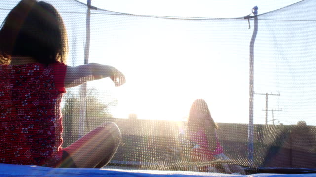 Sisters Bounce zusammen auf einem Trampolin