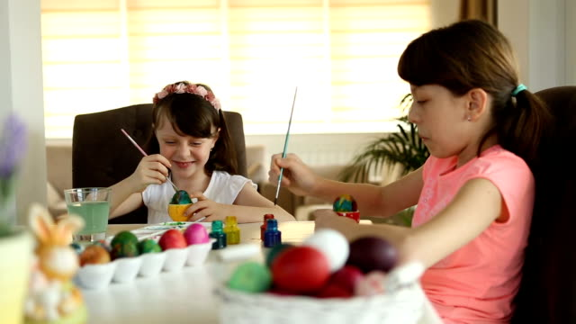 Sisters coloring Easter eggs at home