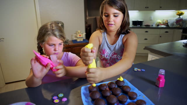 Sisters decorate cupcakes - colorful frosting