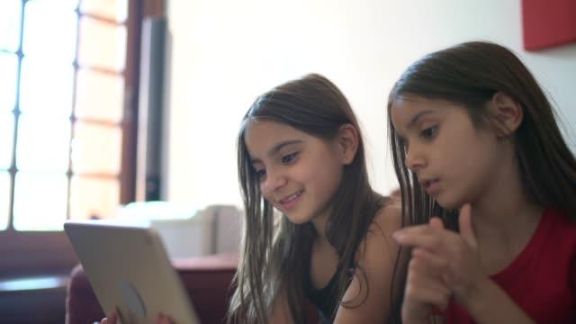 vídeos de stock, filmes e b-roll de irmãs fazendo uma chamada de vídeo usando tablet digital em casa - distante