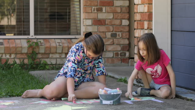 vídeos de stock e filmes b-roll de sisters doing chalk art on driveway - 12 13 anos