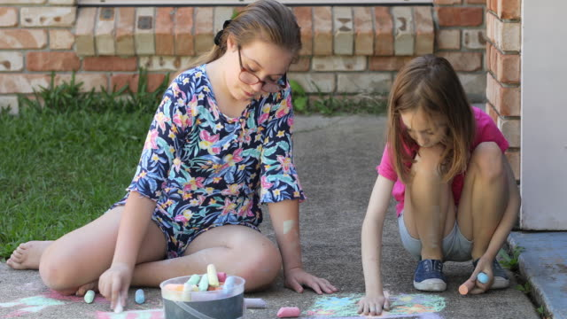 sisters doing chalk art on driveway - chalk art equipment stock videos & royalty-free footage