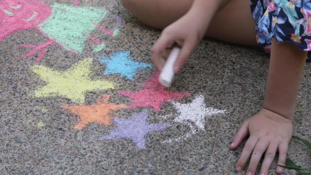 sisters doing chalk art on driveway - pre adolescent child stock videos & royalty-free footage