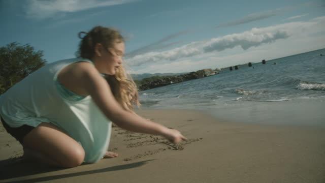 vídeos de stock e filmes b-roll de sisters draw the word aloha on the beach in maui, hawaii. - aloha