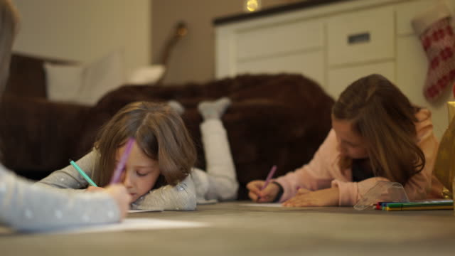 sisters drawing on floor at home