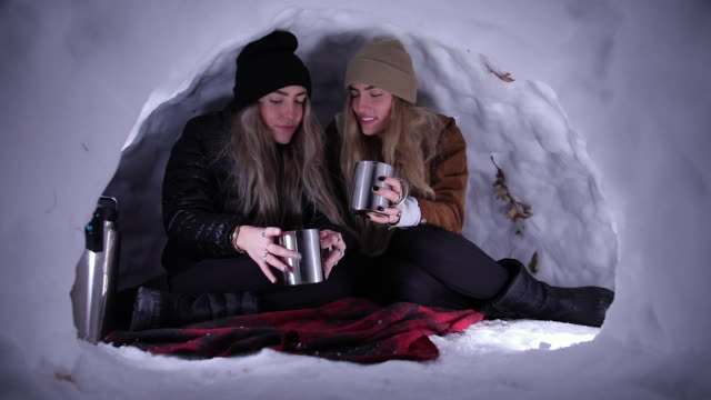 sisters drinking from mugs while in igloo talking - igloo stock videos & royalty-free footage