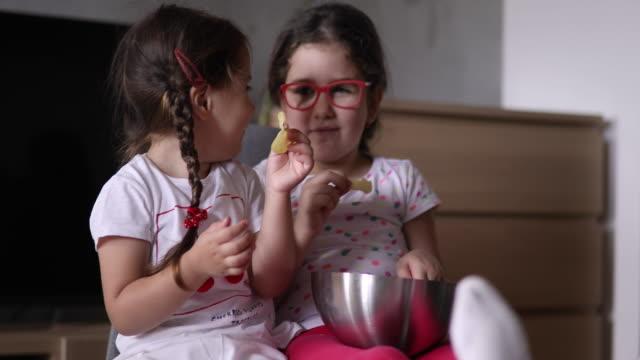 vídeos y material grabado en eventos de stock de hermanas comiendo aperitivos juntos - patatas fritas de churrería