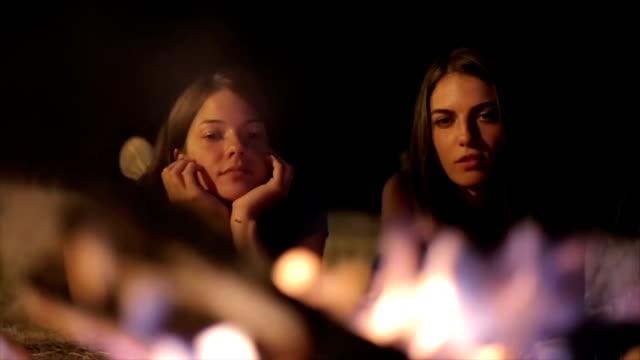 Sisters enjoy camping along campfire