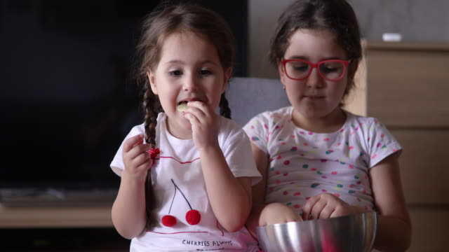 schwestern, die süßen speisen zu hause genießen - gesichtsausdruck stock-videos und b-roll-filmmaterial