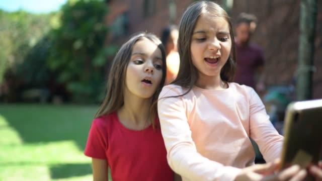 sorelle che si filmano ballando, usando lo smartphone - dependency video stock e b–roll