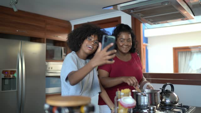 sisters filming themselves while cooking at home - live broadcast stock videos & royalty-free footage