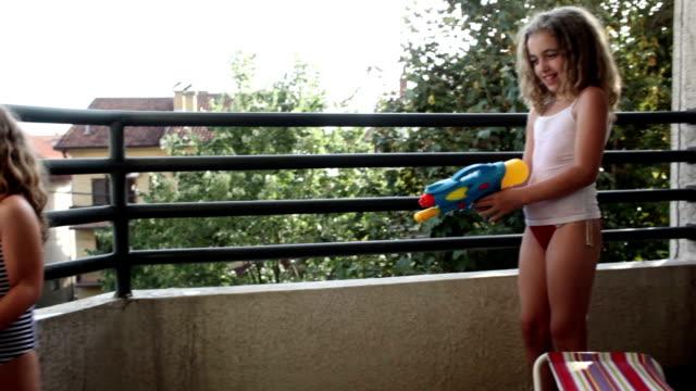 hd: schwestern, die spaß mit wasser waffen - kind vor der pubertät stock-videos und b-roll-filmmaterial