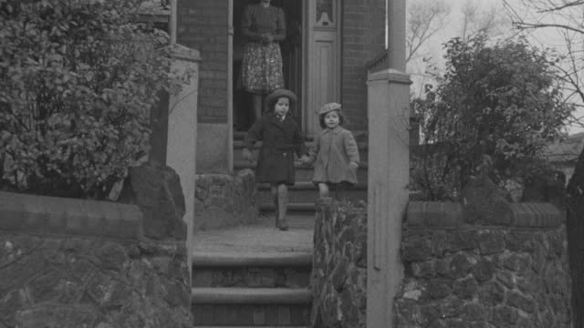 1947 ts sisters holding hands while leaving house / united kingdom - black and white stock videos & royalty-free footage