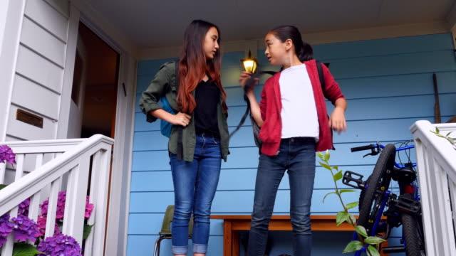 ms sisters in discussion on front porch of home before leaving for school - popolazione dell'asia orientale video stock e b–roll