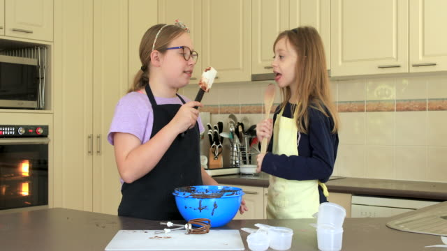 sisters licking chocolate of the wooden spoon after baking - spoon stock videos & royalty-free footage