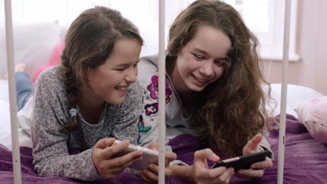 Sisters looking at their smartphones in bedroom