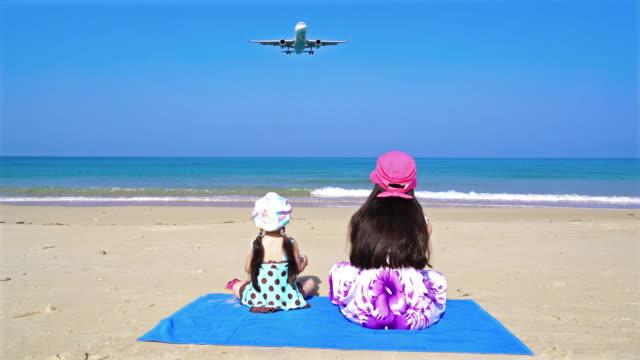 stockvideo's en b-roll-footage met zusters op zoek het vliegtuig landing op zee - militair vliegtuig