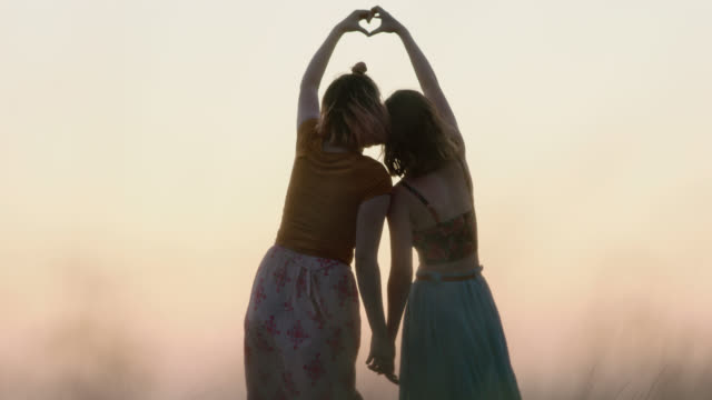 vidéos et rushes de ws slo mo. sisters make heart shape with hands in open field at magic hour. - onirique