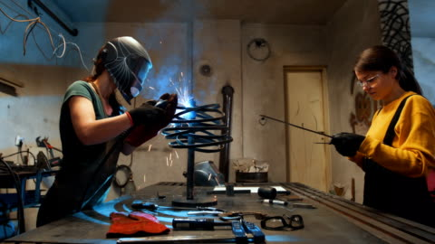 sisters making art out of metal - welding stock videos & royalty-free footage