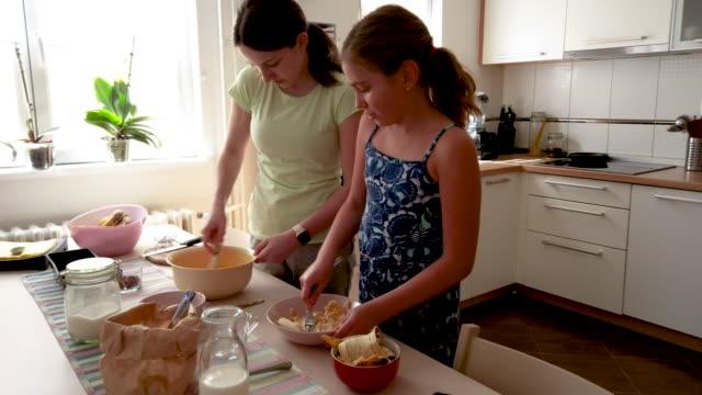 vídeos de stock, filmes e b-roll de irmãs fazendo pão de banana na cozinha - irmã