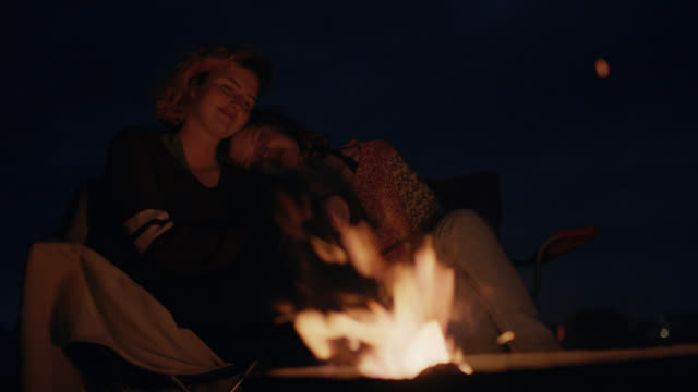 WS. Sisters on camping trip lean on each other and watch as fire sparks and crackles in the dark.