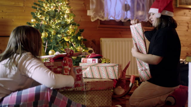 4K Sisters opening Christmas gifts near Christmas tree, real time