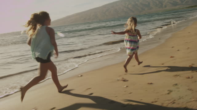 Sisters playing and running on the beach in Maui, Hawaii.