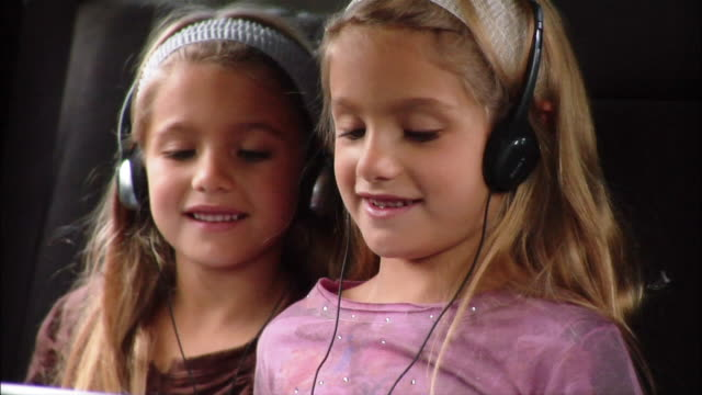 sisters playing game on portable dvd player - dvd player stock videos & royalty-free footage