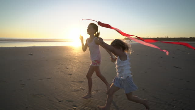 WS SM sisters playing on the beach at sunset