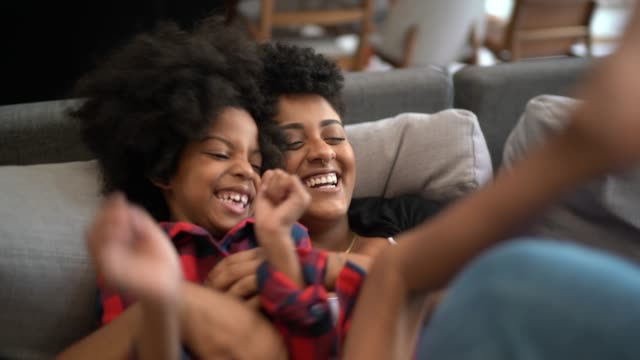vídeos de stock e filmes b-roll de sisters playing on the couch, tickling each other - aconchegante