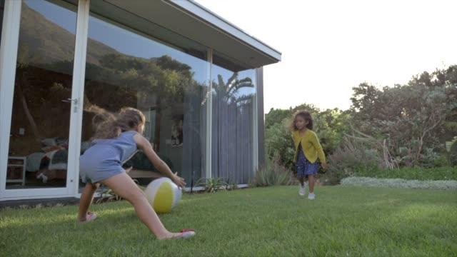 vidéos et rushes de sisters playing with ball in backyard - jardin de la maison