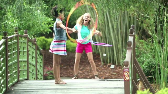 Zusters spelen met hula hoops