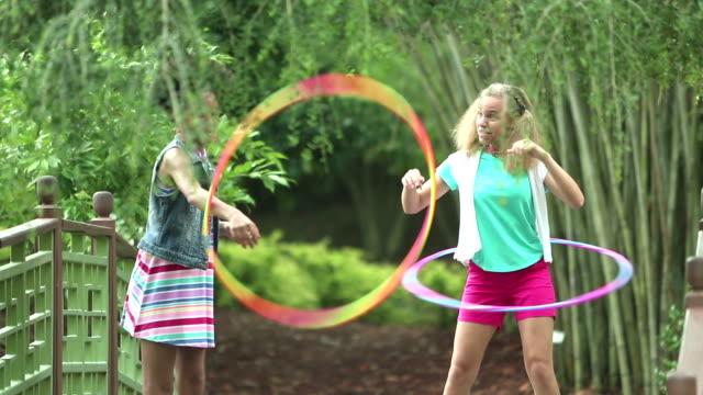 schwestern spielen mit hula hoops - dreiviertelansicht stock-videos und b-roll-filmmaterial