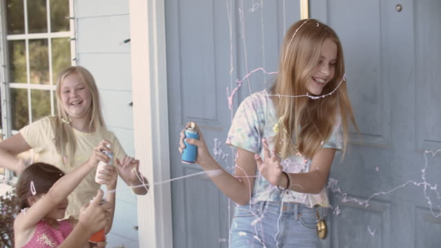 sisters playing with party string at home - geschwister stock-videos und b-roll-filmmaterial