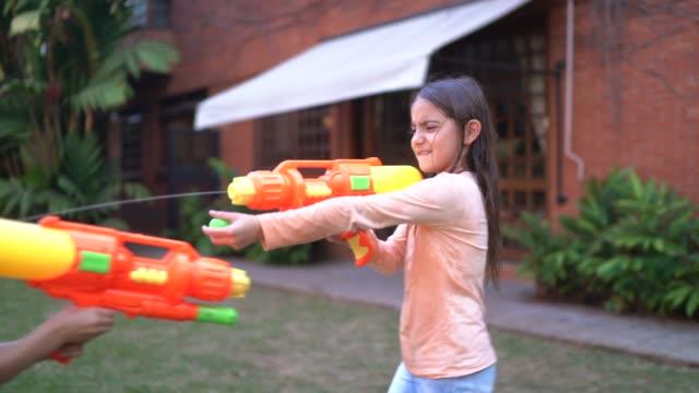 schwestern spielen mit spritzpistole im hinterhof - battle stock-videos und b-roll-filmmaterial