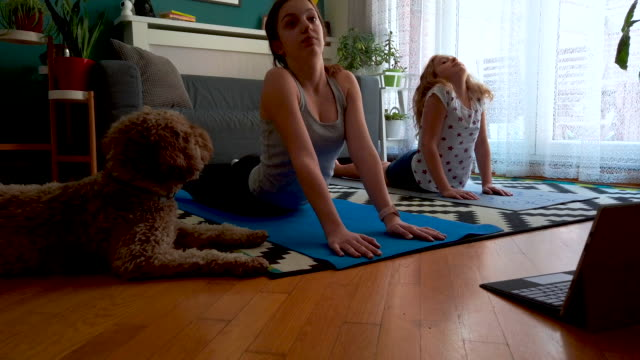 sisters practicing yoga at home with instructor online - competition stock videos & royalty-free footage