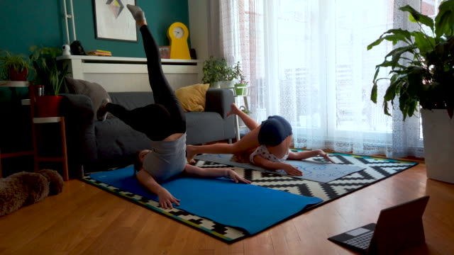 sisters practicing yoga at home with instructor online - yoga stock videos & royalty-free footage