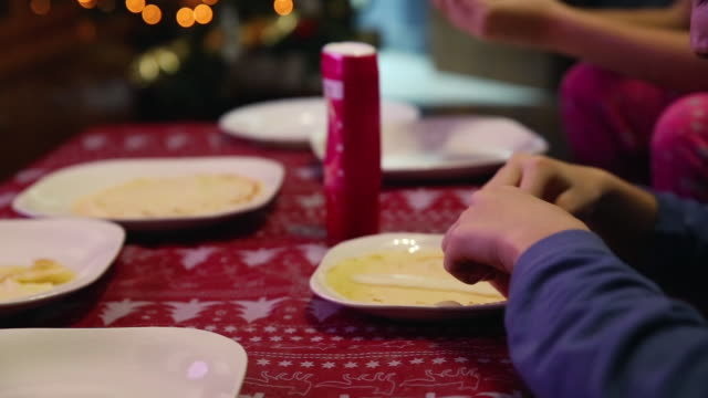 sisters preparing and eating breakfast next to the christmas tree - nightwear stock videos & royalty-free footage
